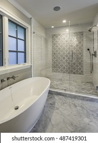 Master Bathroom with large tub and tiled shower and marble floors