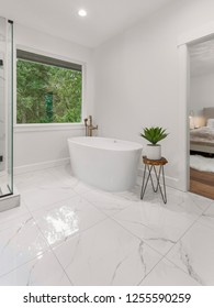 Master Bathroom in New Luxury Home: Features Elegant Floor and Bathtub, with Partial View of Shower and Master Bedroom