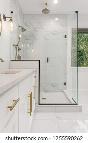 Master Bathroom in New Luxury Home: Features Elegant Shower with Glass Door, Multiple Shower Heads, Sink with Vanity, and Elegant Tile Floor