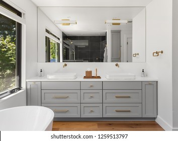 Master Bathroom in New Luxury Home: Features Double Vanity with Cabinets and Two Sinks, Large Mirror and Partial View of Bathtub