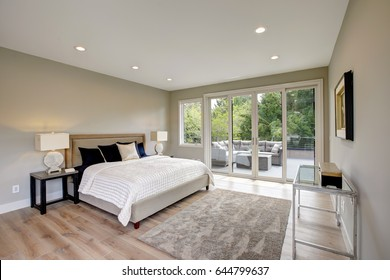 Master bedroom interior with private balcony in a new construction home. Northwest, USA