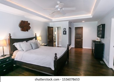 Master bedroom with king size bed and tray ceilings with uplighting and hradwood floors
