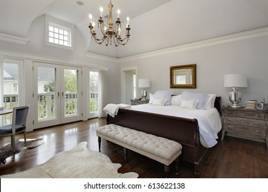 Master bedroom in luxury home with doors to balcony.