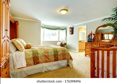 Master bedroom with round corner, carpet floor, queen size bed and carved wood cabinets with mirror
