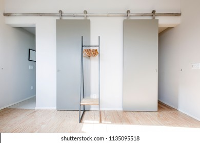 Master bedroom showing linear lines with barn doors and clothes rack