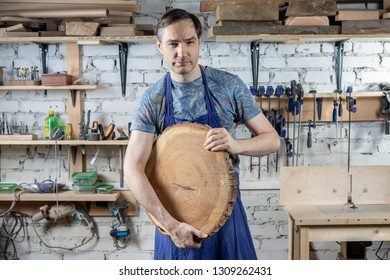 Master carpenter in an apron in his workshop. Small business