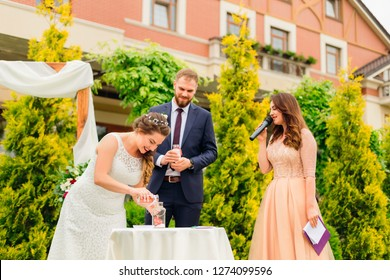 the master of ceremonies holds a sand ceremony and newlyweds in turn pour in unity vase sand of different colors. wedding sand ceremony