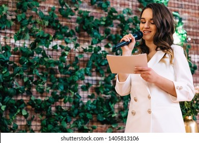 The master of ceremonies reads a speech. woman in a white suit with a beautiful makeup