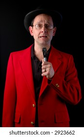 Master of Ceremonies talking to a microphone over a black background.