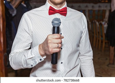 Master of ceremonies in a white shirt and with a red bowtie holding a microphone in his hand, Master of ceremonies with microphone