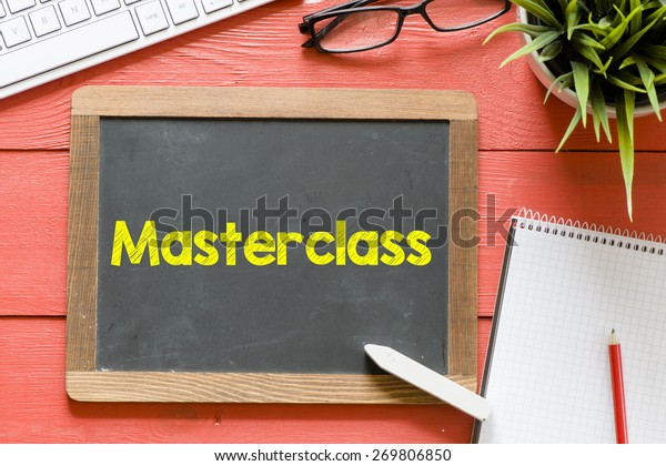 Master class handwritten on blackboard. Master class Handwritten with chalk on blackboard, keyboard,notebook,glasses and green plant on wooden background