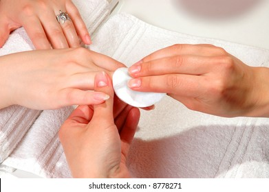 Master cleaning the nail of a woman