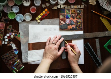 The master in the creative workshop is working on the product, enamel for metal, drawing. Concept creativity and handwork, toning and soft focus, real interior.