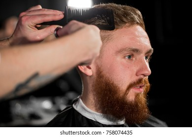 Master cuts hair and beard in the Barber shop. Hairdresser makes hairstyle using scissors and a metal comb