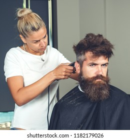 Master cuts hair and beard of men, beauteous woman hairdresser makes hairstyle for man with beard. Hipster brutal bearded male. Female hairdresser cutting hair of smiling man client at beauty salon