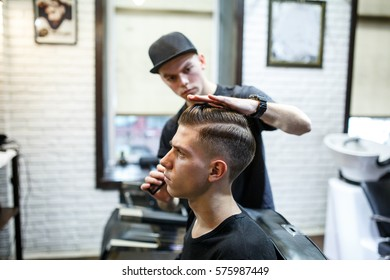 Master cuts hair of men in the barbershop, hairdresser makes hairstyle for a young man.