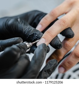 The master does hardware manicure in the beauty salon. Removal of the gel varnish with a milling cutter, removing the pterygium and cuticle with a remover, applying gel shellac varnish with a design.