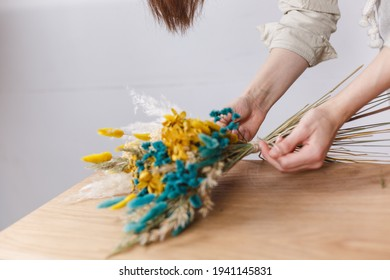 Master florist makes a bouquet of dried flowers at the master class, workshop