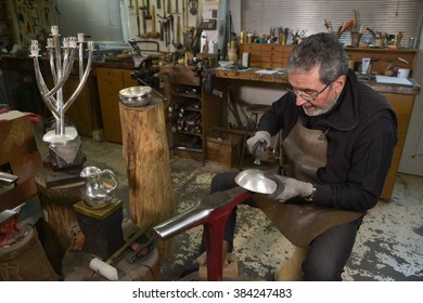Master goldsmith working with silver-Shaping of the object by hammering