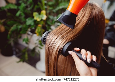 master in a hairdresser dries her hair to a girl with a hairdryer and makes a styling