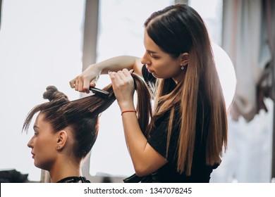 Friseur-Meister macht Haarmädchen mit Haartrockner und Haarpflegeprodukten