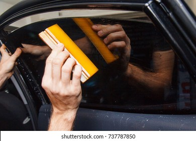 Master installs a tint film for the car glass with a hairdryer and spatula with glare of light. Concept tinting
