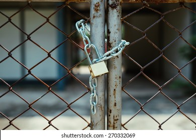 Master key and chain with rusty fence background