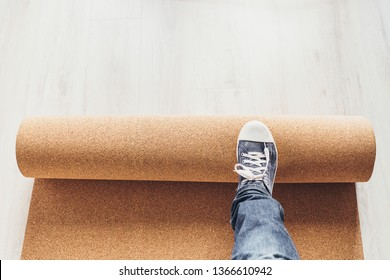 The master lays the cork substrate on the floor before laying the flooring - installation of the laminate