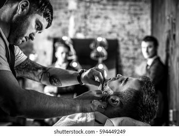 Master makes beards correction in barbershop salon. Black-white photo.