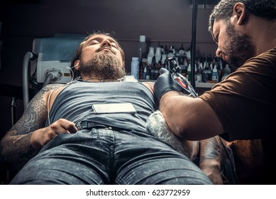 Master makes tattoo pictures in salon./Tattoo specialist doing tattoo in tattoo parlour.
