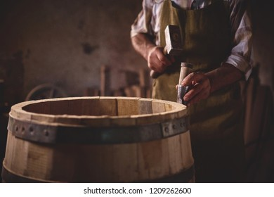 the master makes a wooden barrel for brandy, oak boards compresses them with iron rings