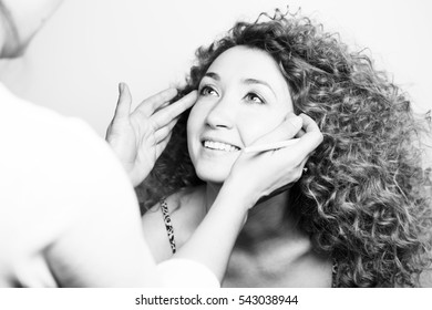 master of make-up to apply makeup on the face of a beautiful curly girl, studio black and white photo