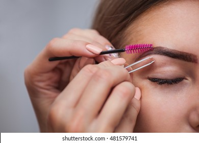 Master makeup corrects, and gives shape to pull out with forceps previously painted with henna eyebrows in a beauty salon. Professional care for face.