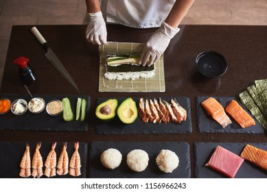 Master making a sushi roll with nori, rice, cucumber and omelet using bamboo mat. Closeup view of process. View from the top
