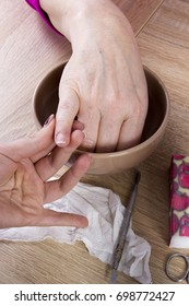 Master in manicure uses a special manicure tool in the beauty salon
