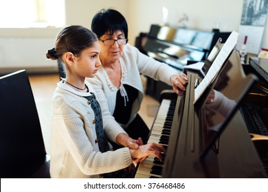 master piano shows the student how to hold his hand