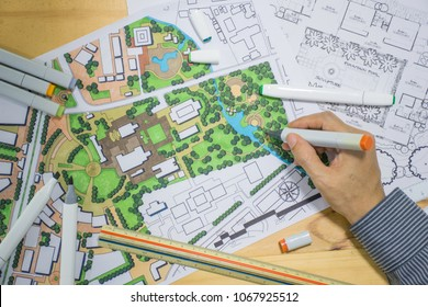 master plan of urban landscape design or urban architecture drawing by man's hand with drawing tools , color markers, scale rulers on the table, selective focus