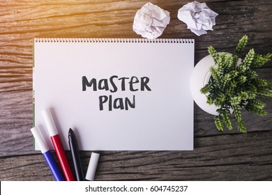 Master Plan word with Notepad and green plant on wooden background