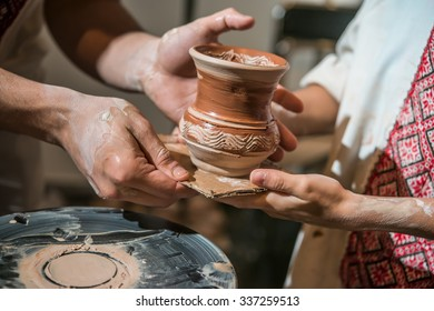 Master potter teaches the child how to make a pitcher on a pottery wheel