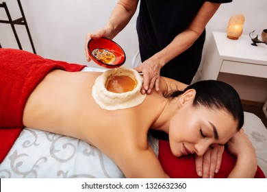 Master pouring oil. Dark-haired relaxed woman experiencing Ayurveda treatment in salon while master adding oil into clay pool on her back
