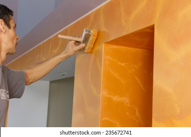 Master in the process of applying textured paint on the wall.