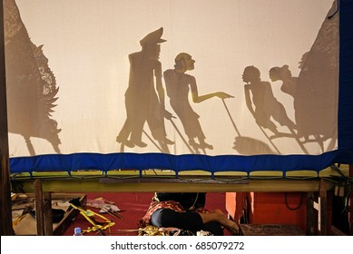 A master puppet is performing a shadow puppet show accompanied by Javanese gamelan orchestra