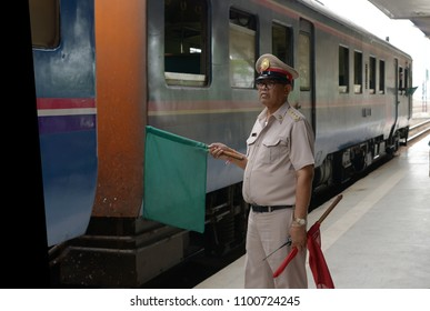 Master railway station gave the signal to train driver Departure Station.He send signal green flag to pass,train departure from train station. Udon thani ,Thailand 27 may 2018