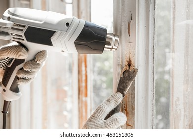 Master removes old paint from window with heat gun and scraper. Closeup
