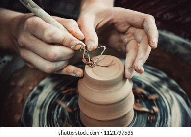 Master removes the top layer of clay on pot with a special tool. Create clay vessel. Modeling white-clay, shaping vessel. Caucasian man making vessel. Clay in circle.