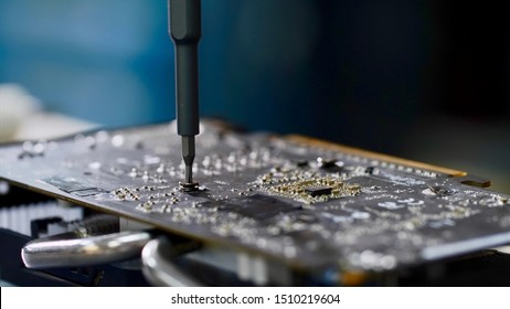 Master repairs of computer equipment, establishing chip and circuits. PC technician screws chipset of graphics card to ventilator installing it, hands closeup. PC repair and maintenance in workshop.