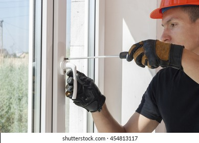 master with a screwdriver sets fittings on the window