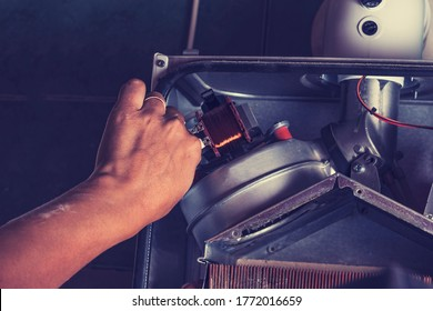 The master sets up a gas boiler, which weighs on the wall. The front dashboard is open. The removal and installation of an exhaust gas turbine from the system takes place.