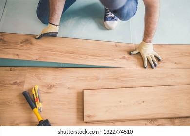 The master skillfully and professionally puts laminate flooring