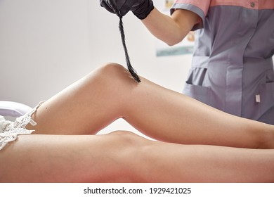 Master of sugaring procedure with delicate feather on smooth legs. Concept of medicine, medical instruments, health care, beauty industry, hair removal, natural material